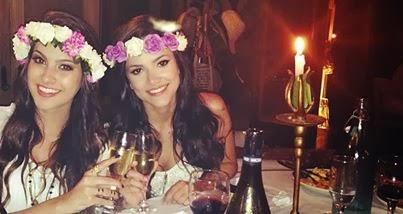 Foto da blogueira Nah Cardoso e cantora Manu Gavassi em um restaurante. Ambas usam uma blusa branca, coroa de flores e seguram uma taça de champanhe sorrindo.