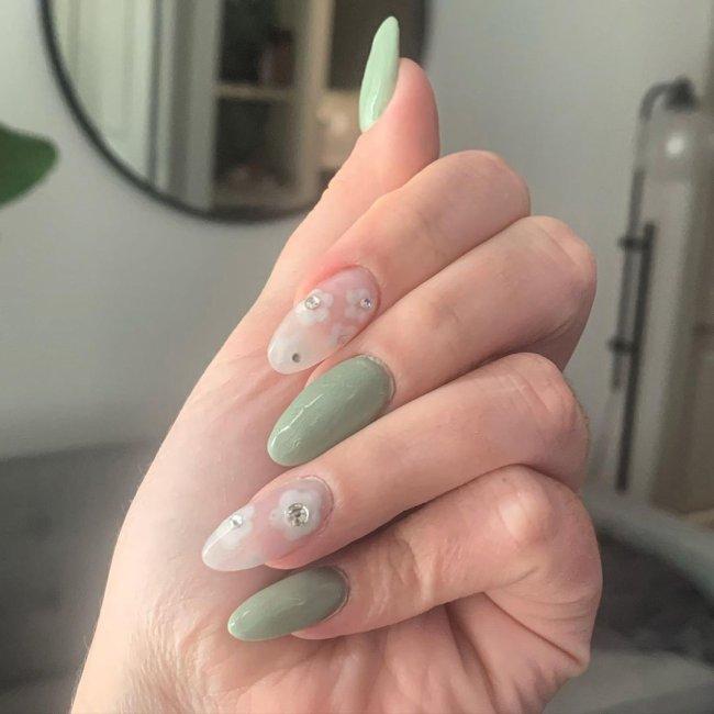 Foto com close nas unhas e tem nail art com desenho de flor branca com bolinha verde.