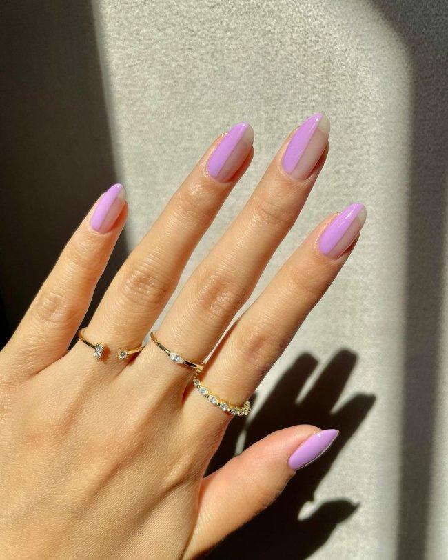 Foto com close nas unhas e tem nail art com traços na cor lilás.