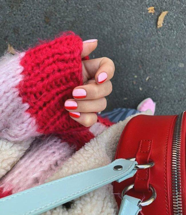 Foto com foco nas mãos mostrando nail art rosa com detalhes vermelhos. Também podemos ver uma parte da blusa de tricô com detalhes em vermelho e rosa e uma parte da bolsa na cor vermelha.