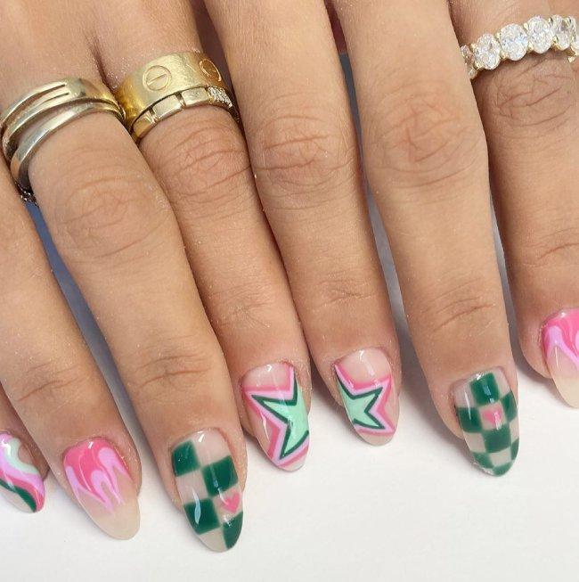 Foto com close nas unhas e tem nail art com desenho xadrez, e estrelas. Nas cores rosa, verde escuro e verde claro.