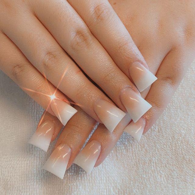 Foto com foco nas unhas com formato duck feet. As unhas estão esticadas. Com francesinha branca.
