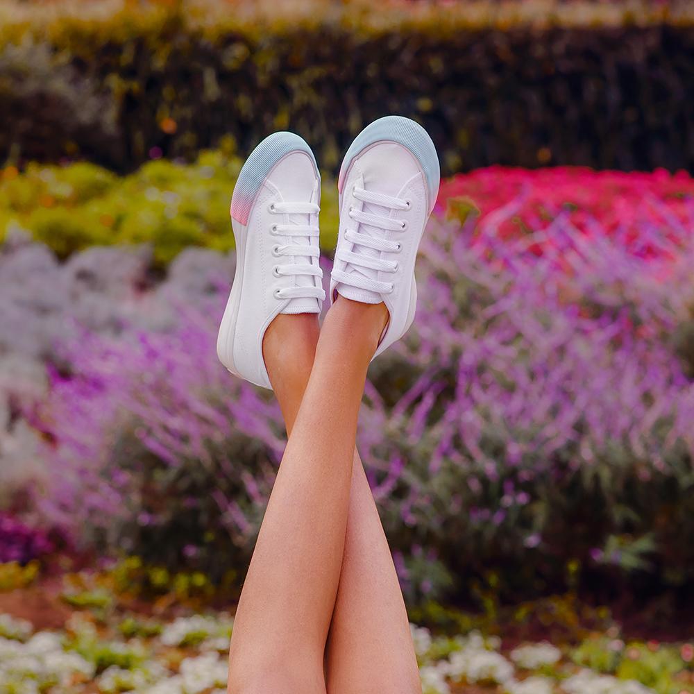 Garota com os pés para cima usando tênis branco com detalhe em azul da coleção da CAPRICHO Shoes. Na foto, só dá para ver as pernas e, ao fundo, há uma paisagem de grama e flores.