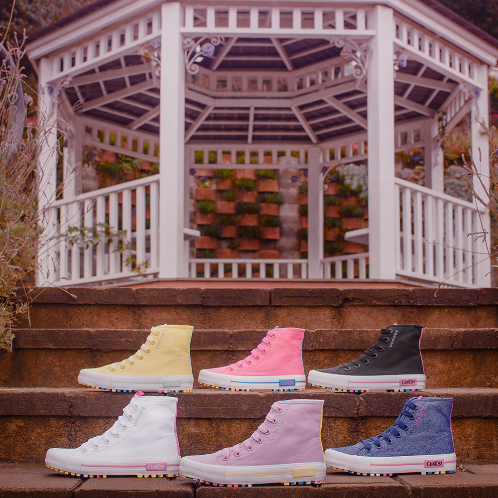 Foto com seis tênis de cano alto da coleção da CAPRICHO Shoes em uma escada com um gazebo branco ao fundo. No degrau de cima, estão os tênis amarelo, rosa e preto e, no de baixo, os tênis branco, lilás e jeans.