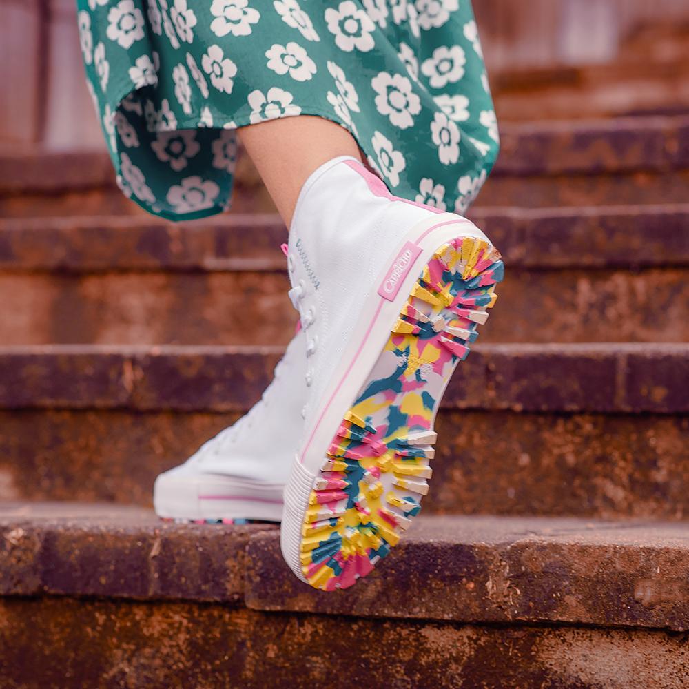 Foto do pé de uma menina usando tênis branco de cano alto da CAPRICHO Shoes com sola toda colorida. Ela está em um degrau de uma escada e dá para ver um pedaço do seu vestido longo verde com flores.