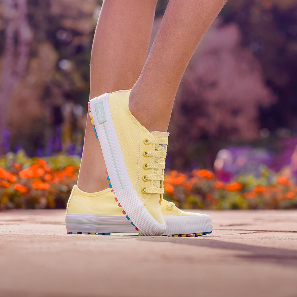 Garota usando tênis amarelo com sola colorida da coleção da CAPRICHO Shoes. Na foto, dá para ver os pés dela no chão, e um deles está na frente com a ponta do tênis tocando o chão.