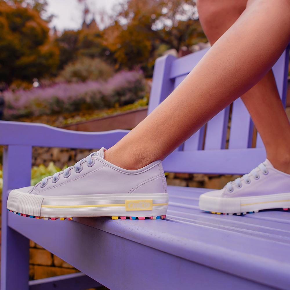 Garota usando tênis lilás com sola colorida da CAPRICHO Shoes. Na foto, dá para ver os pés dela, que estão apoiados em um banco lilás.