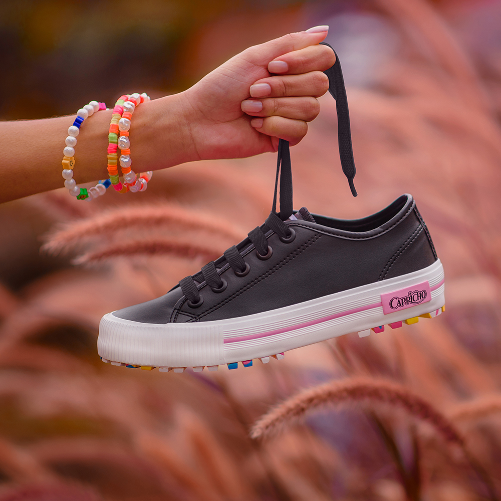 Garota segurando pelo cadarço o tênis preto com branco e sola colorida da CAPRICHO Shoes. Na foto, dá para ver apenas uma de suas mãos segurando o sapato.