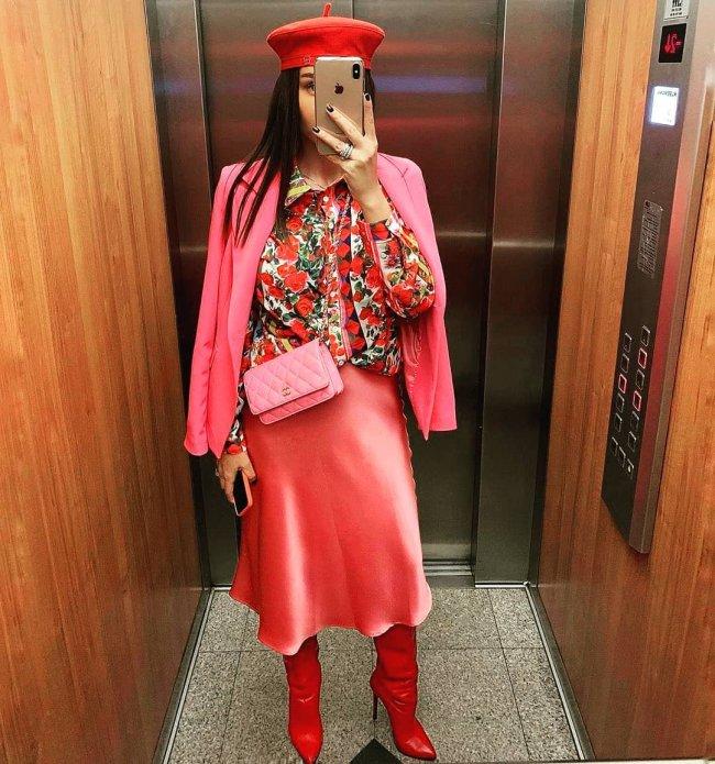 Jovem tirando foto em elevador, mostrando seu visual com boina, camisa estampada, blazer rosa e saia.