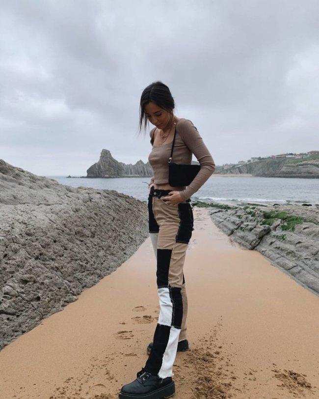 Jovem posando na praia com blusa marrom e calça com patchwork com detalhes em preto e marrom, ela olha para baixo e uma de suas mãos segura o cós da calça.