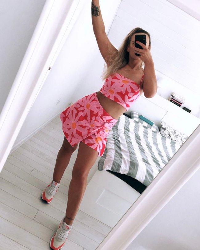 Jovem posando com a mão esquerda levantada e apoiada na parede, enquanto ela tira selfie mostrando seu celular preto para o espelho. Tamb´pem podemos ver alguns detalhes de seu quarto como a cama branca e as paredes. Ela usa conjunto florido com as cores rosa e vermelho.