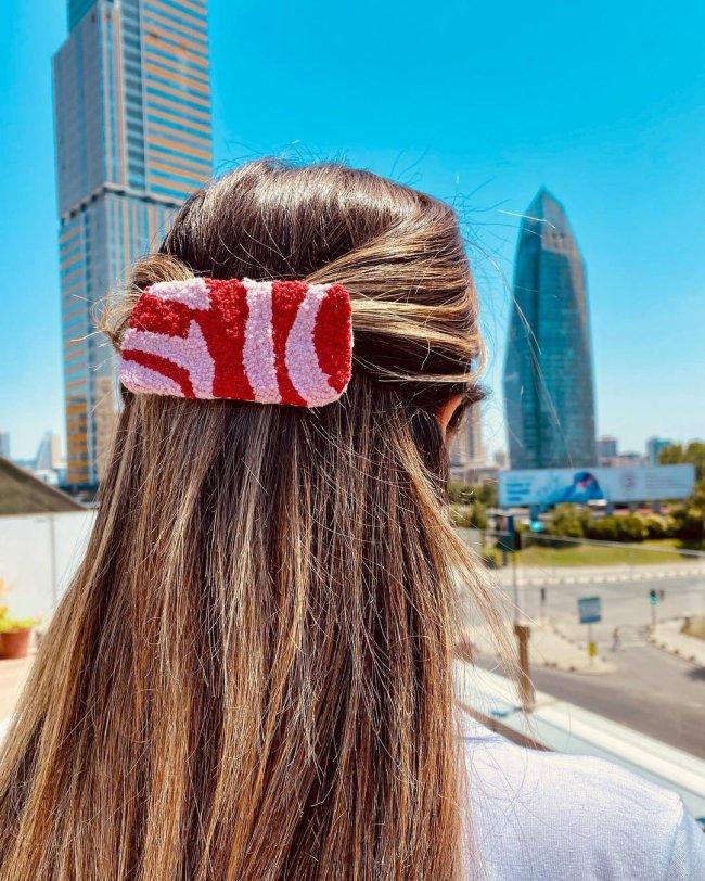 Na imagem só podemos ver alguém de costa, com o cabelo preso com uma presilha rosa com detalhes em vermelho.
