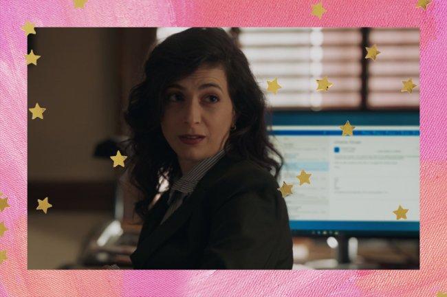 Rebecca Sherman olhando por cima do ombro em cena do reboot de Gossip Girl; ela usa um blazer preto por cima de uma camisa listrada; a margem é uma textura em tons de rosa com estrelas amarelas como decoração