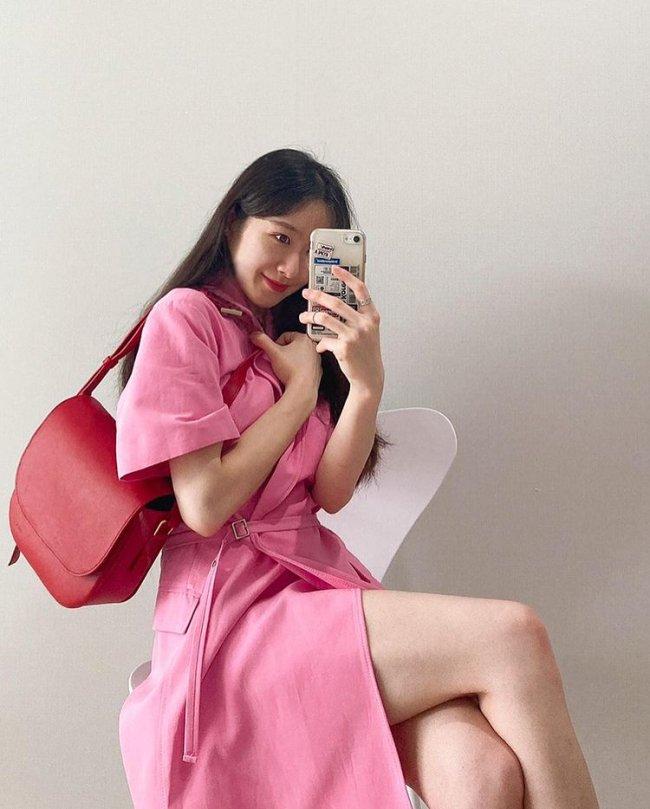 Jovem sentada em uma cadeira branca, ela aponta o celular para o espelho e seu look é composto por vestido rosa e uma bolsa vermelha que está pendurada em seu braço esquerdo.