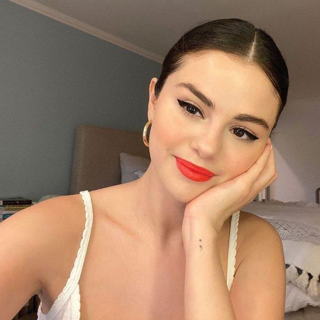 Selfie da atriz e cantora Selena Gomez. Ela usa uma blusa de alcinha branca, brinco de argola dourado, cabelo preso em um coque e maquiagem com delineado preto e batom vermelho. Ela olha para a câmera, sorri e apoia o rosto na mão esquerda.