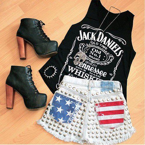 Foto de um look com regata preta com estampa Jack Daniels, short com estampa da bandeira dos Estados Unidos e sapato LITA.