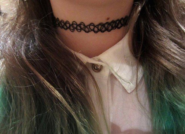 Foto do pescoço de uma menina. Ela usa uma gargantilha que imita uma tatuagem.