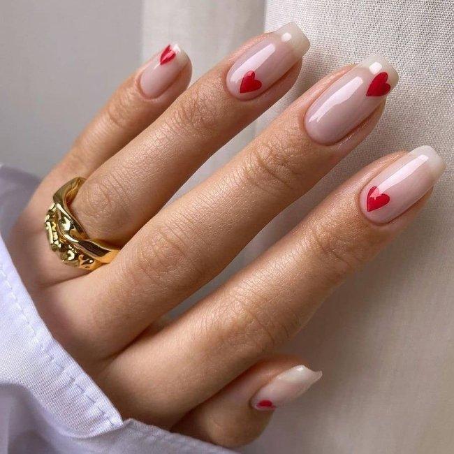 Foto com foco nas mãos exibindo a nail art das unhas. No caso, corações vermelhos.