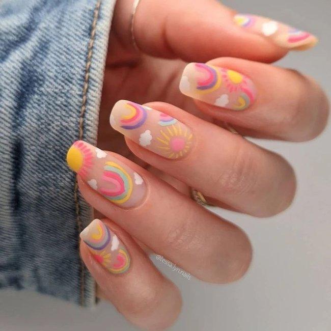 Foto com close nas unhas e tem nail art com desenhos de arco-íris, nas cores, azul, verde, amarelo, lilás e rosa.