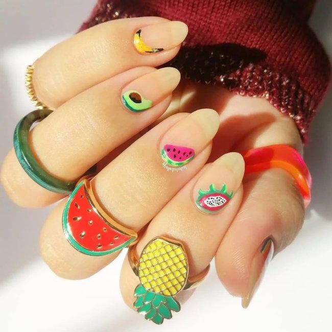Foto com close nas unhas e tem nail art com desenhos de frutas como melancia, abacaxi, kiwi, abacate e banana.