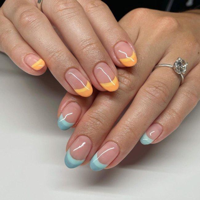 Foto com close nas unhas e tem nail art com francesinha colorida laranja e azul.