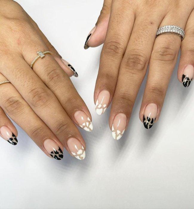 Foto com close nas unhas e tem nail art com espaço negativo nas cores preta e branca.