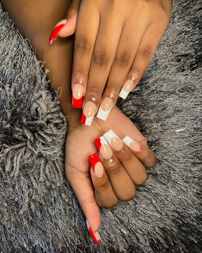 Foto com close nas unhas de duas mãos. Ela está com francesinha branca e vermelha nas unhas.