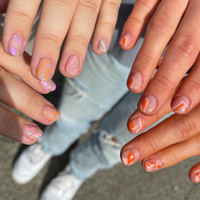 Foto com close nas unhas e tem nail art com as cores laranja, verde e lilás.