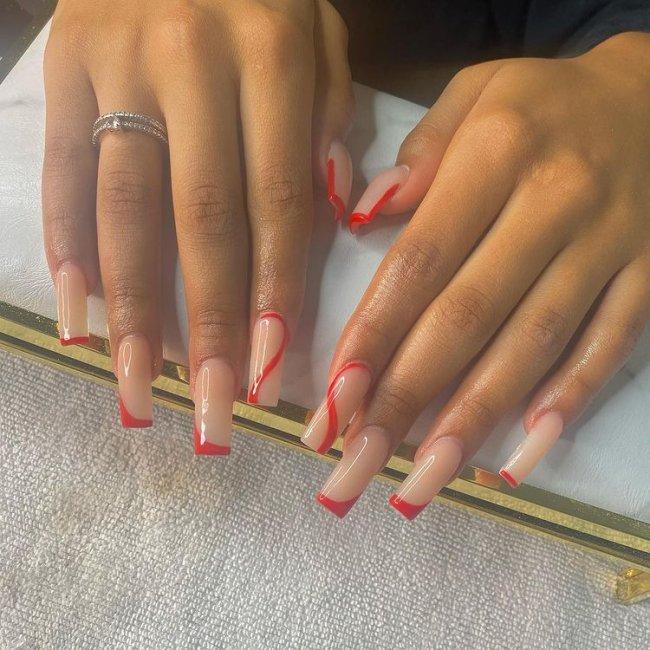 Foto com destaque em duas mãos esticadas mostrando as unhas com base e traços na cor vermelha.