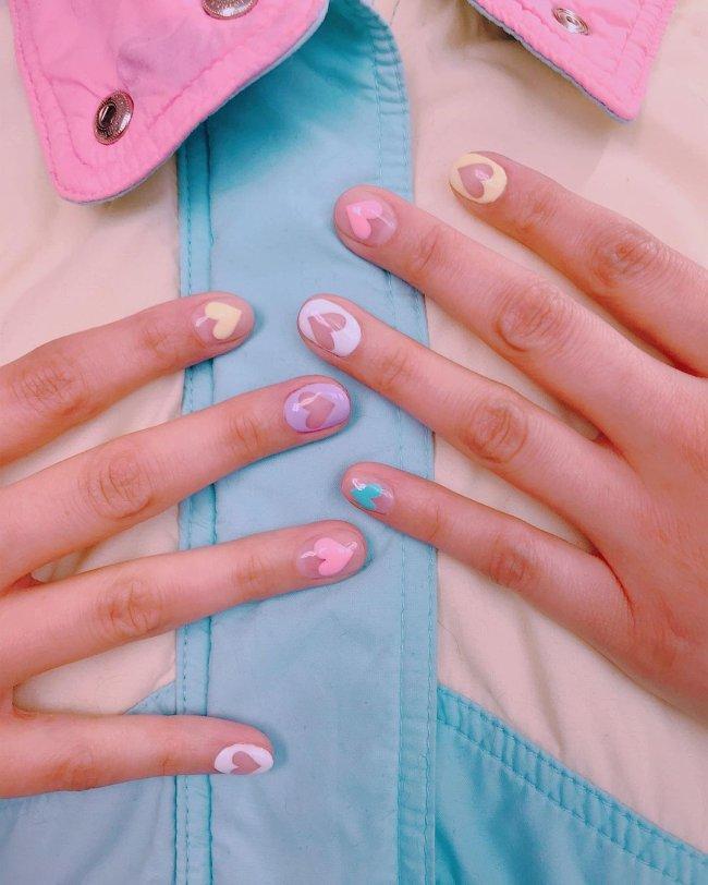 Foto com close nas unhas e tem nail art com corações rosa, lilás, amarelo e verde.