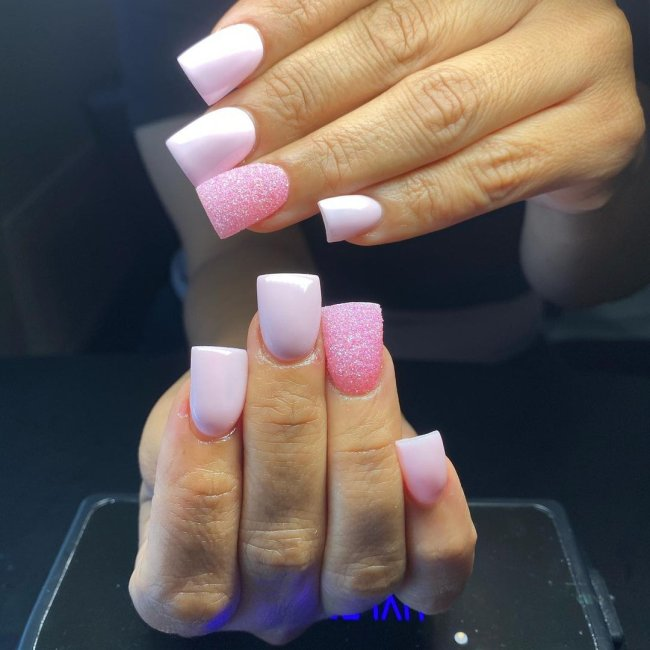 Foto com foco nas unhas com formato duck feet. As unhas estão esticadas. Com degrade rosa e branco.