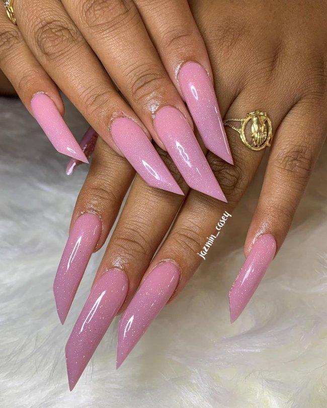 Foto de uma mão com unhas em formato de batom na cor rosa.