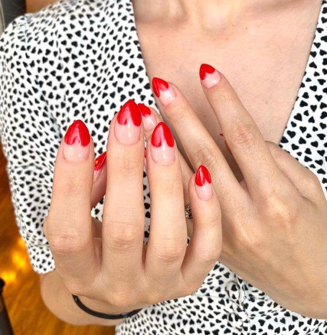 Foto com close nas unhas com desenho de coração vermelho na ponta de cada uma delas.