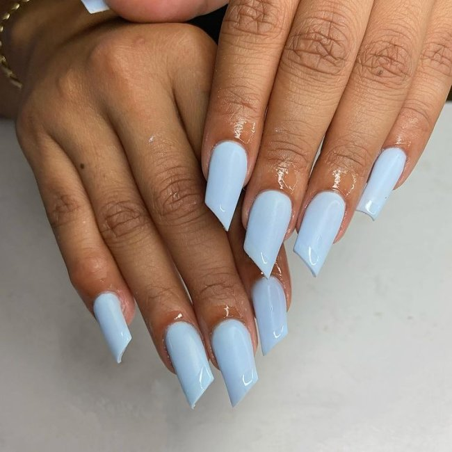 Foto de uma mão com a unha pintada de azul no formato de batom.