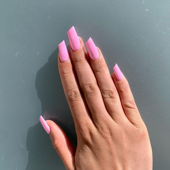 Foto de uma mão com a unha em formato de batom na cor rosa.