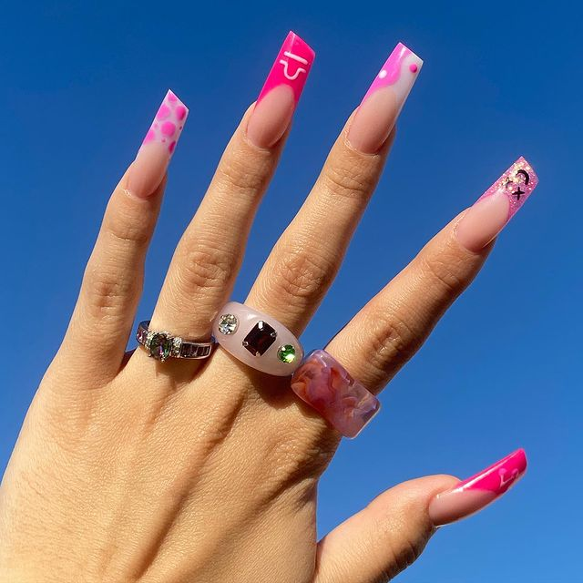 Foto de uma mão com o céu como fundo. A mão está com unhas decoradas em formato de batom e três anéis divertidos.