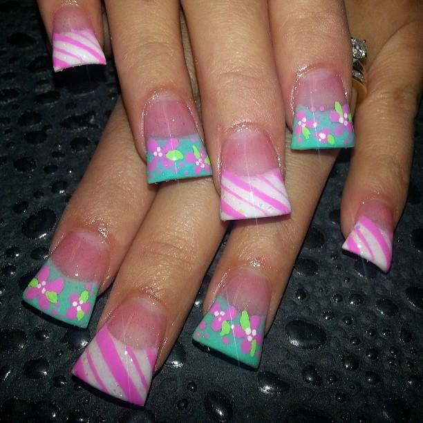 Foto com foco nas unhas com formato duck feet. As unhas estão esticadas. Com glitters coloridos. Com francesinha colorida.