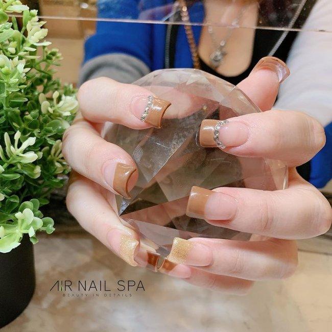 Foto com foco nas unhas com formato duck feet. As unhas estão esticadas. Com francesinha marrom.