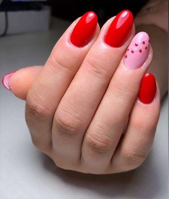 Foto com destaque na mão mostrando as unhas com esmalte vermelho.