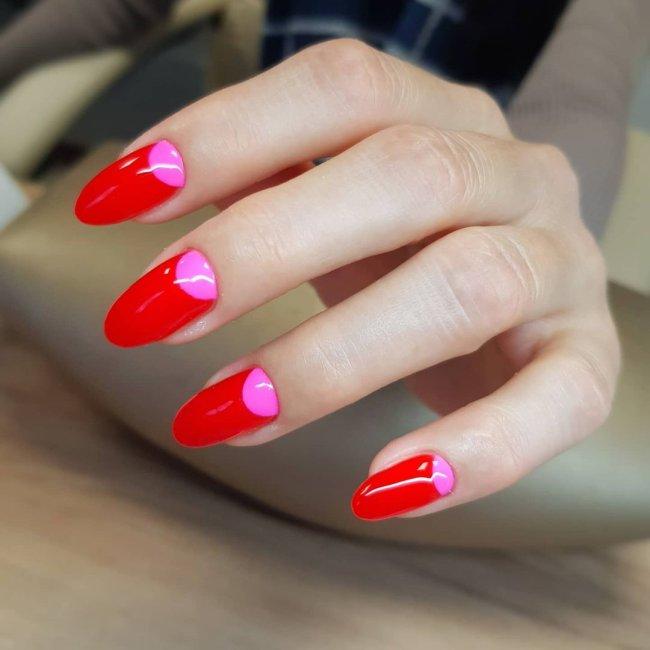 Foto com foco nas mãos mostrando nail art rosa com detalhes vermelhos.
