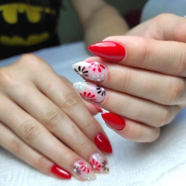Foto com foco nas mãos exibindo a nail art das unhas. No caso, unha vermelha com detalhe de flores.