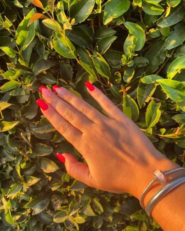 Foto mostrando uma mão apoiada em folhas verdes, nas unhas tem esmalte vermelho com detalhe de strass.