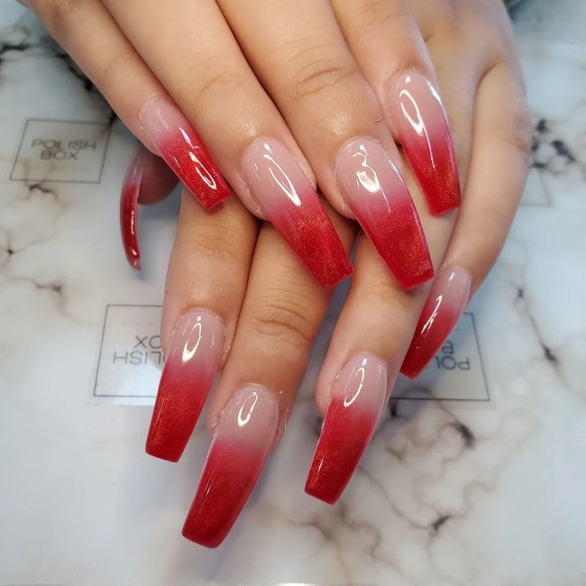Foto com foco nas mãos exibindo a nail art das unhas. No caso, unhas vermelhas com degrade de cor