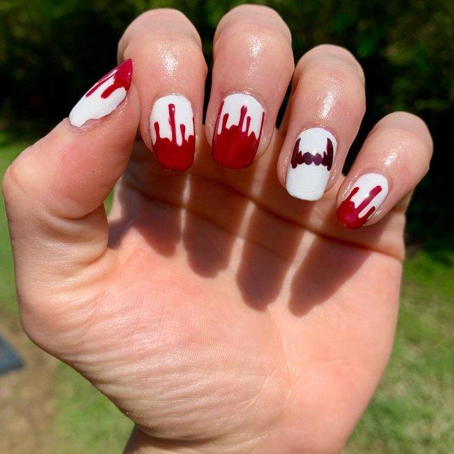 Foto com foco nas mãos exibindo a nail art das unhas. No caso, unhas brancas com detalhe de vermelho nas pontas.