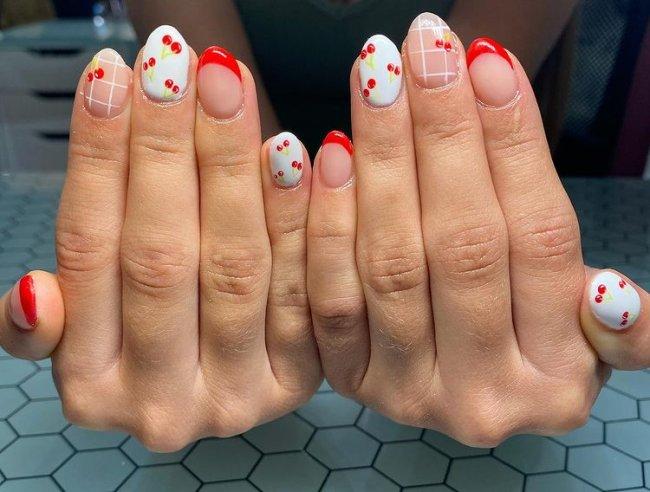 Foto com foco nas mãos exibindo a nail art das unhas. No caso, unhas brancas com detalhes em vermelho e cerejas.