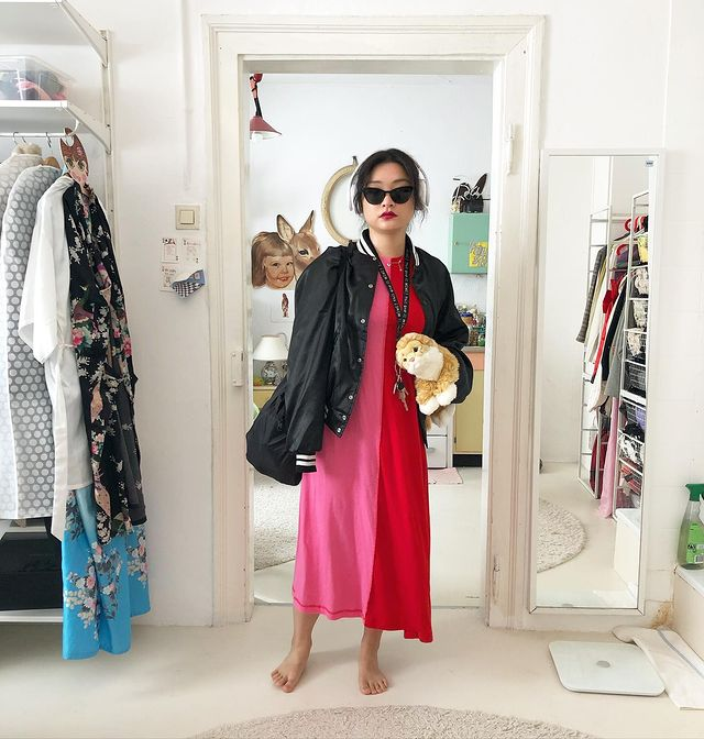 Mulher posando frente a espelho do quarto, podemos ver alguns detalhes do cômodo como as cores brancas da parede e uma arara com roupas. Ela usa vestido metade vermelha e metade rosa, óculos escuros pretos e segura um ursinho de pelúcia.