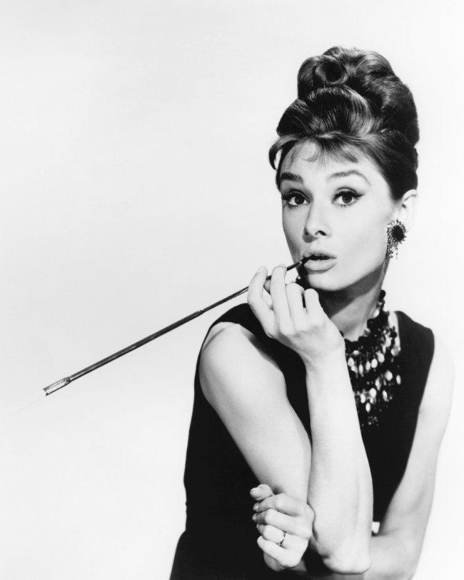 Audrey Hepburn posando com cigarro na boca e virada de lado.