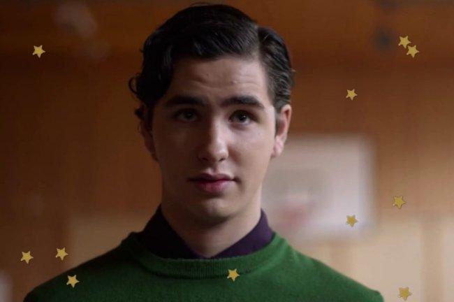 August do seriado Young Royals com blusa verde e expressão séria.