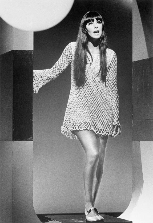 Cher posando com vestido e expressão séria.