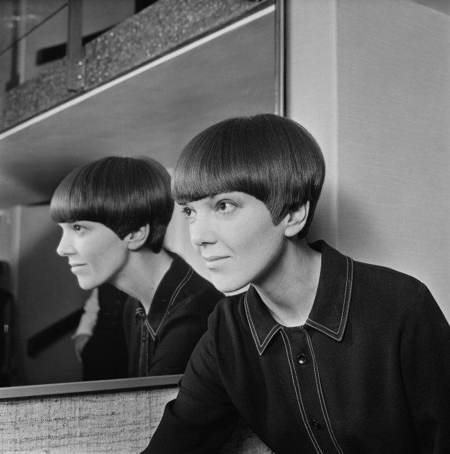 Jovem ao lado de um espelho com expressão levemente sorridente.